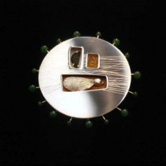 5.92 'Fruits of the Forest' 1997. Brooch; white metal, tourmaline, amber nephrite